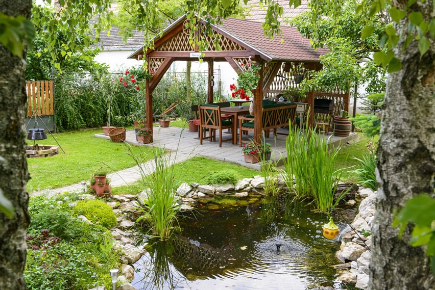 Backyard water feature pond with outdoor dining canopy
