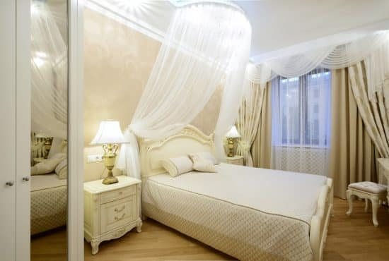beautiful white bedroom with sheer bed curtains