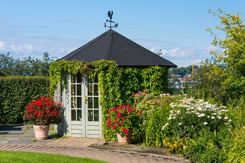 Glass door gazebo in flower garden