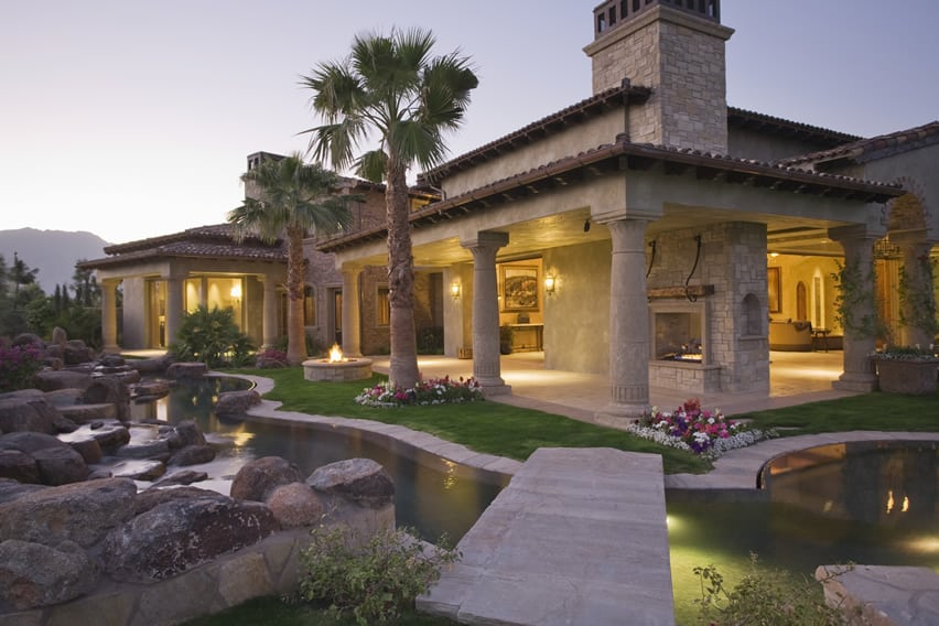 Luxury home backyard with garden pond and flower beds