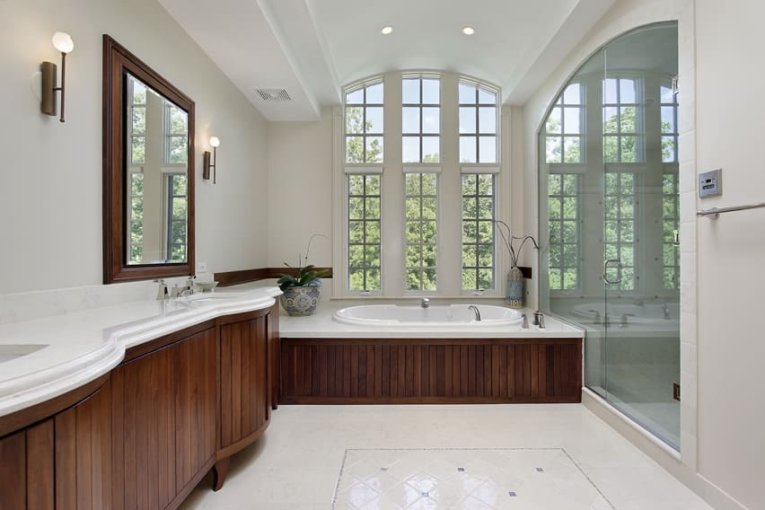 Master bath with vanity using white marble countertops and large glass arched shower