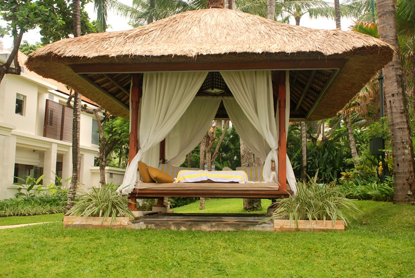 Thatched resort gazebo with curtains and cushions