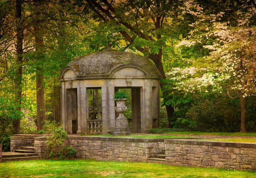 Stone gazebo under trees in park