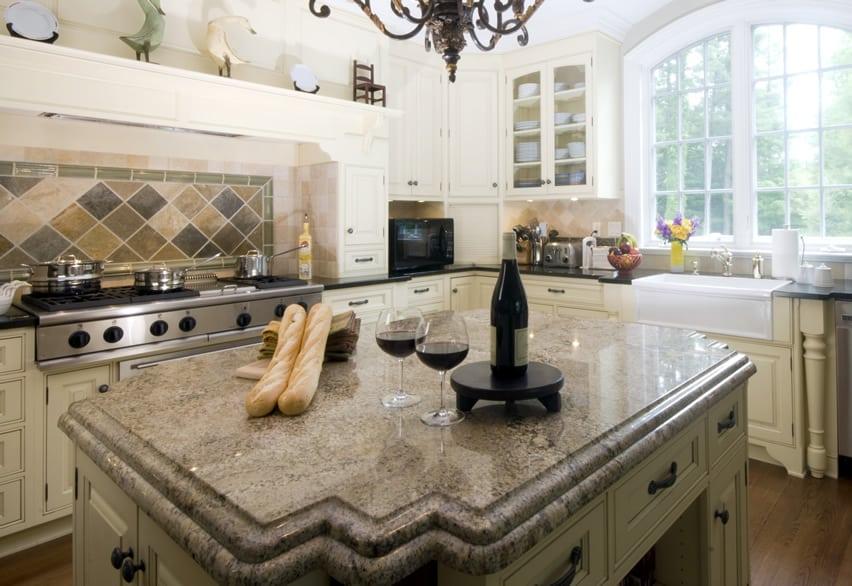 Granite kitchen island with cream cabinetry
