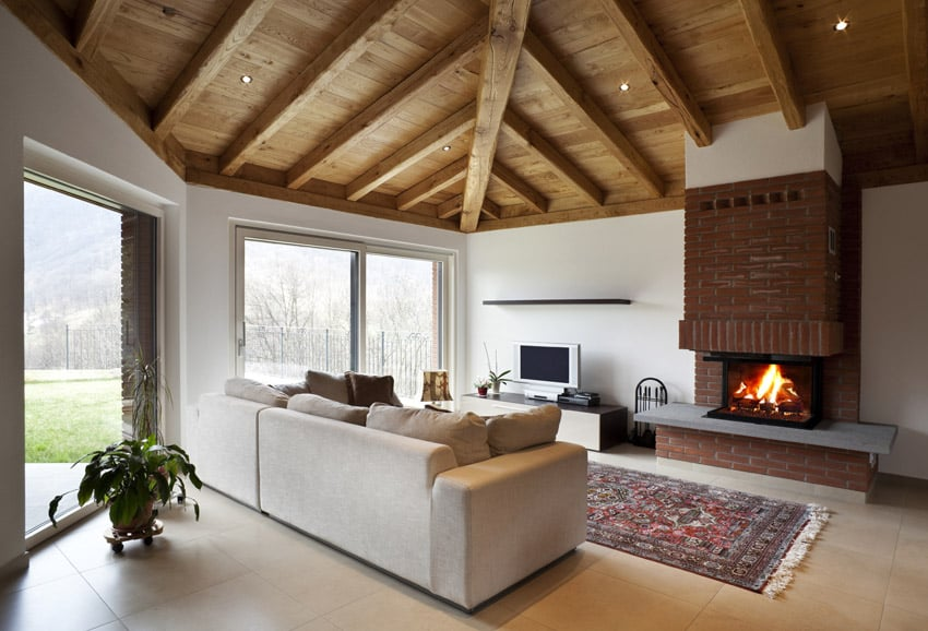 High wood ceiling in living room with fireplace