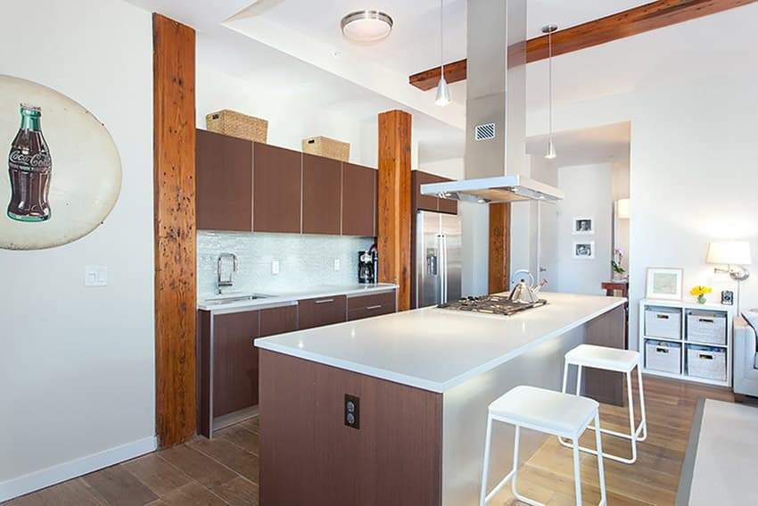 Modern cabinets in kitchen with white solid surface counters