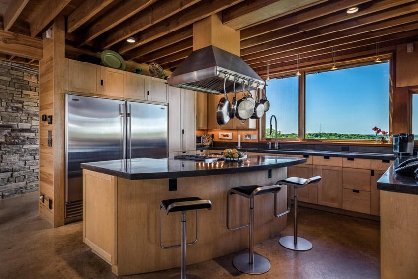 Chefs wood kitchen with dining island, large oven hood and black counters