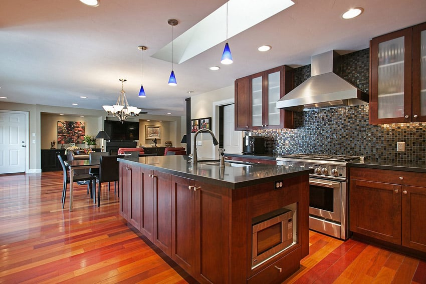 Kitchen with bright wood flooring and blue pendant lights