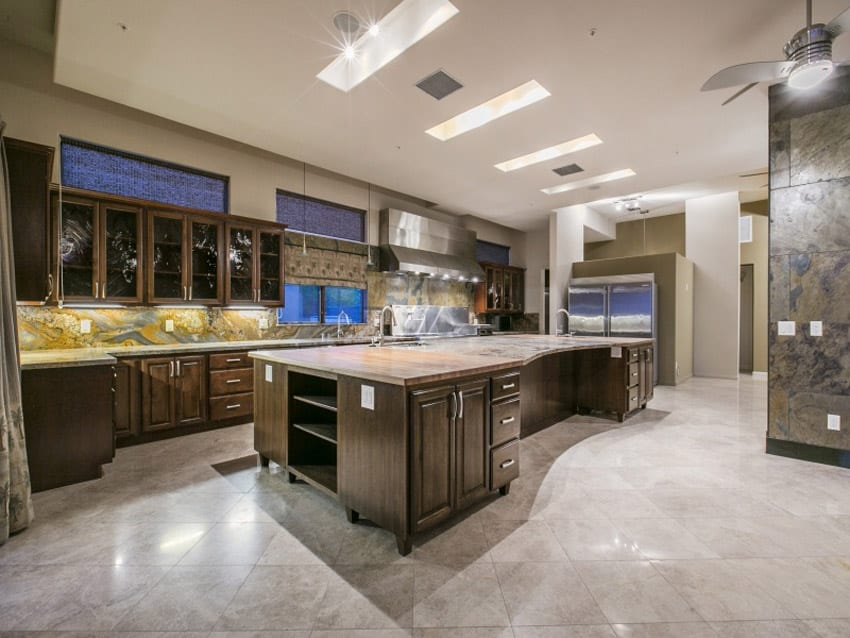 L shaped kitchen with slate backsplash granite counters and upscale finishes