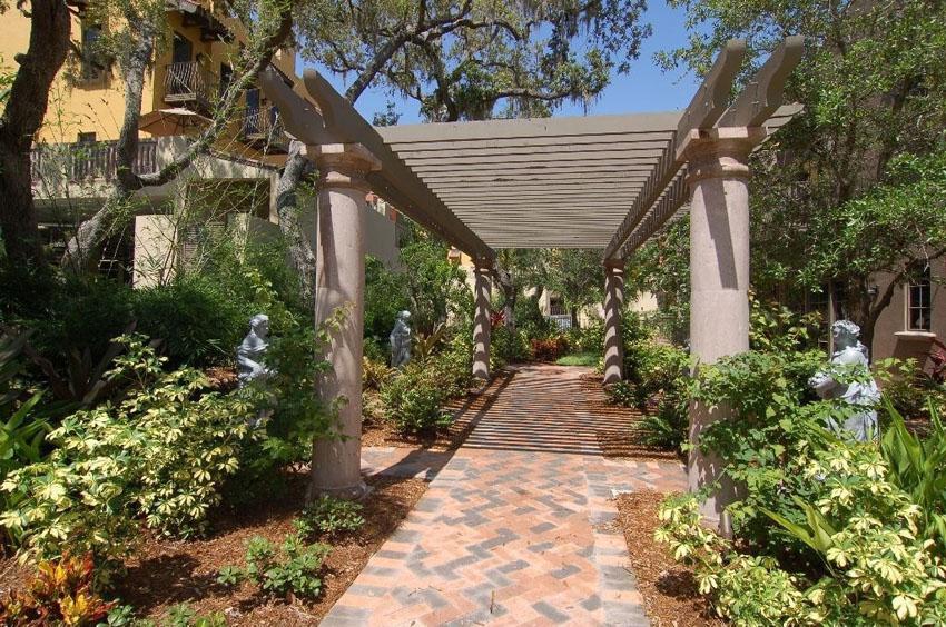 Brick paver walkway under trellis with decorative pillars