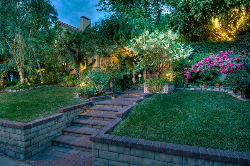 Brick walkway with steps and brick topped retaining wall through garden