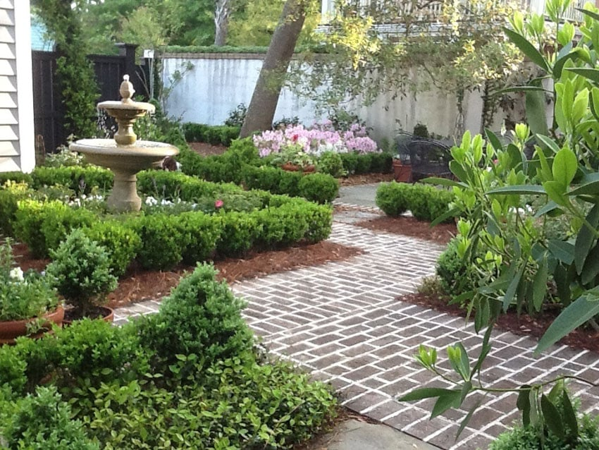 Concrete walkway by fountain and landscaped garden