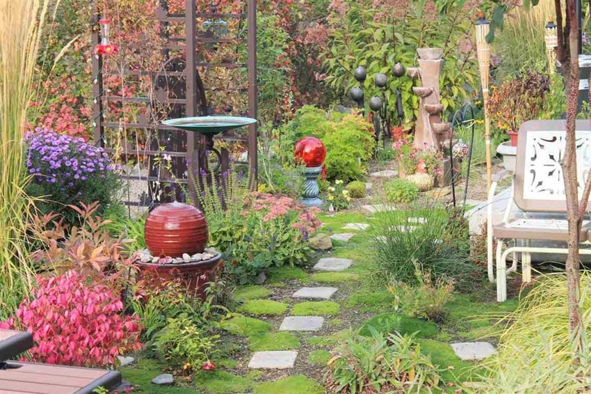 Grey square patio stones through garden with arbor