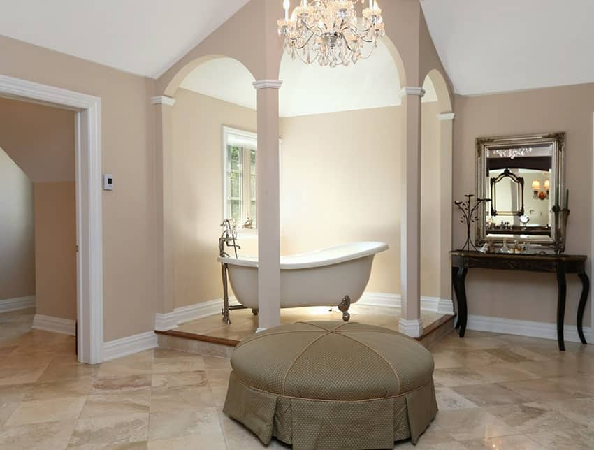 Raised clawfoot bathtub in bathroom with chandelier