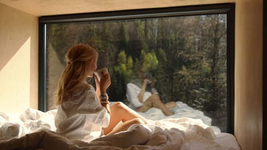 Girl in micro apartment suspended bedroom with view