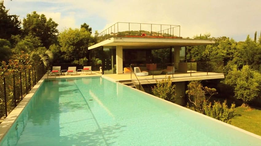 Modern concrete home with elevated swimming pool