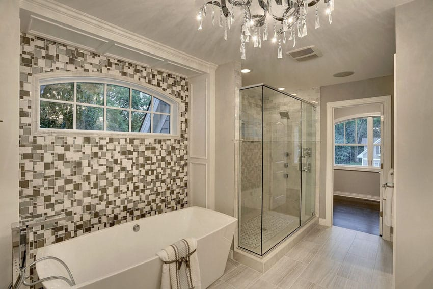 Contemporary master bathroom with acrylic tub mosaic accent wall and porcelain tile floors