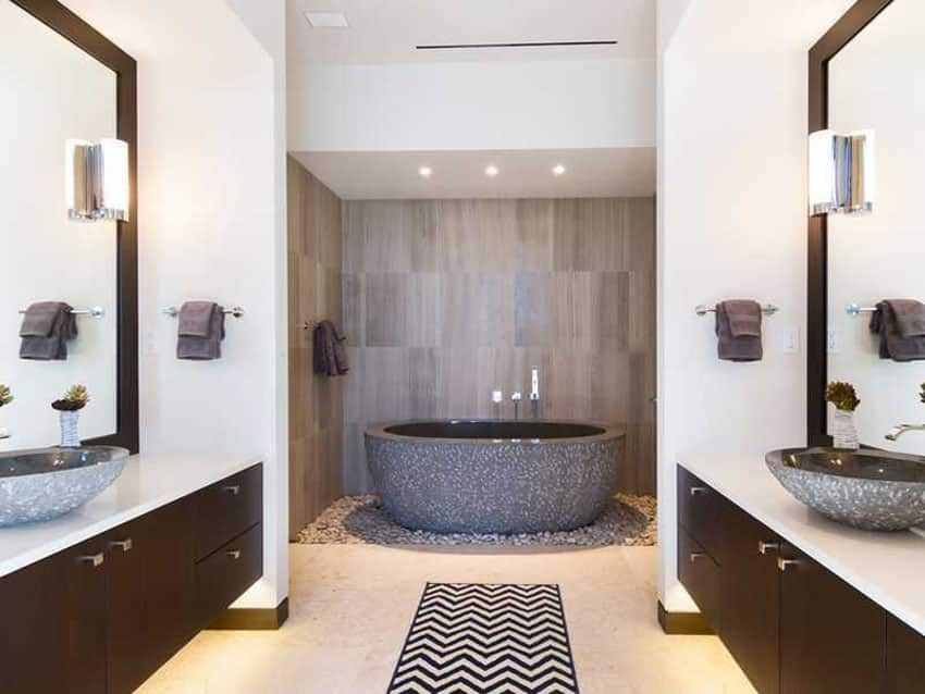 Contemporary master bathroom with custom chiseled stone bathtub surrounded by river rock