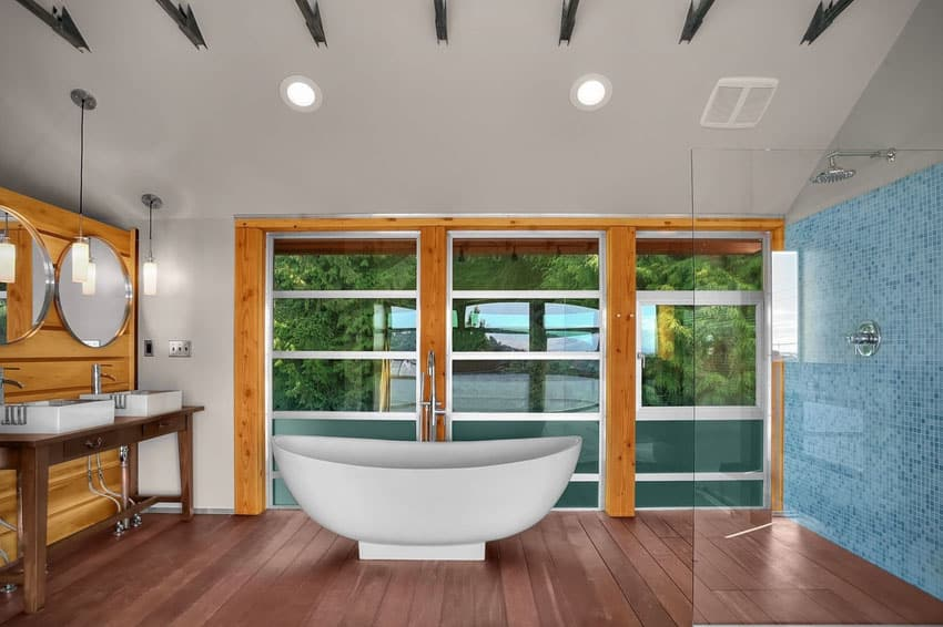 Contemporary master bathroom with gel coated bathtub and window views of trees