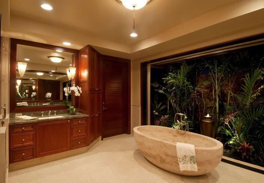 Contemporary master bathroom with sandstone bathtub and tropical plants