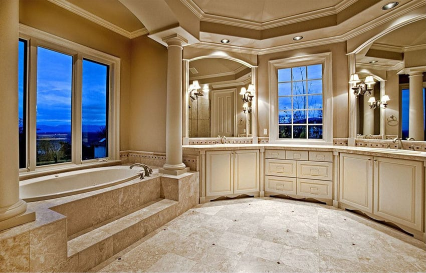 High end master bathroom with elevated bathtub with views and marble flooring tray ceiling