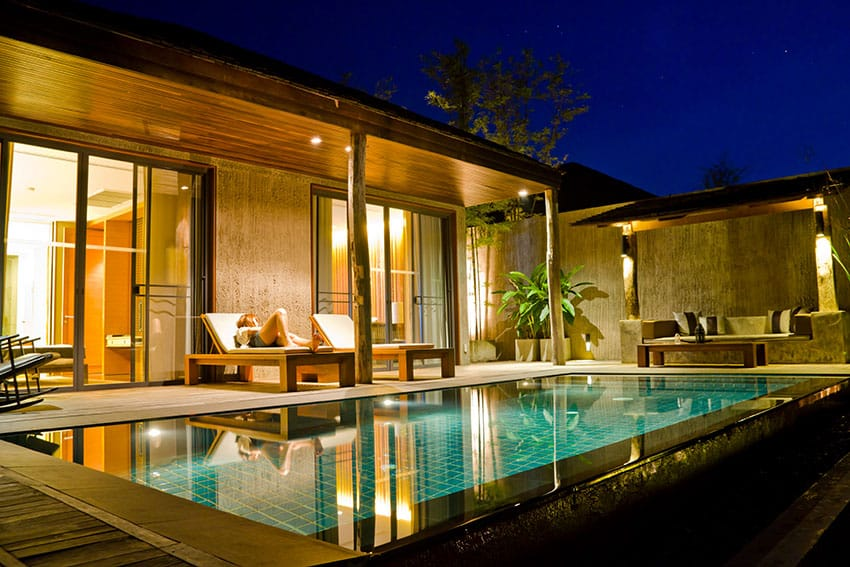 Luxury swimming pool patio with covered roof and lounge chairs