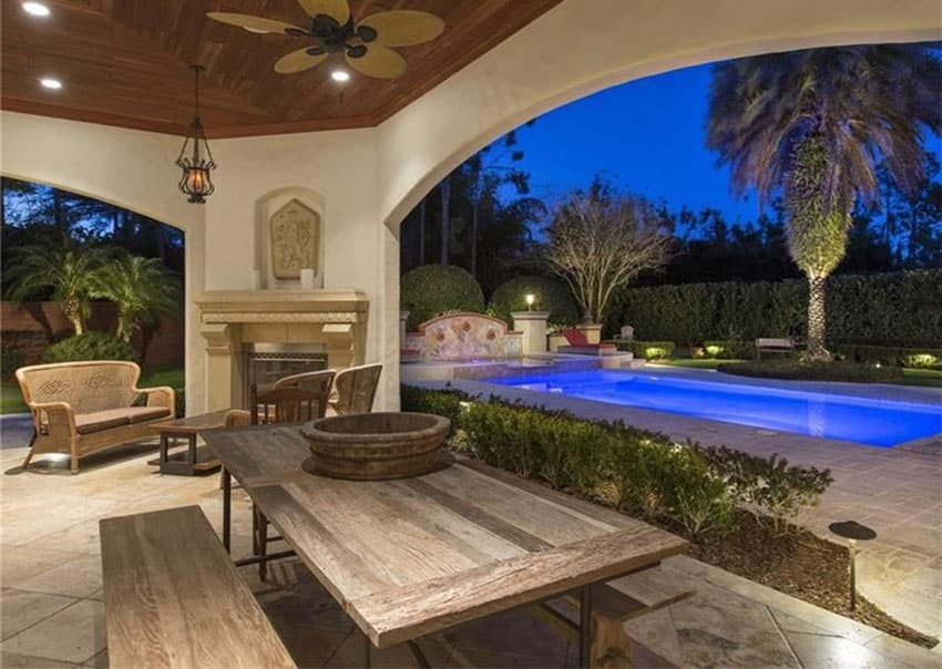 Mediterranean patio with rustic picnic table fireplace and view of pool