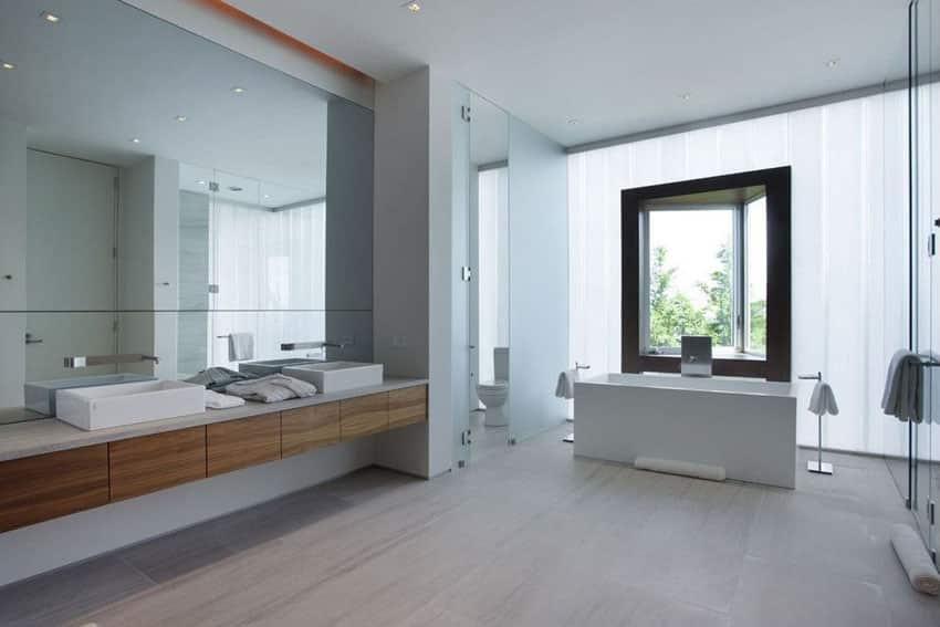 Modern master bathroom with skirted straight edge bathtub and floating vanity