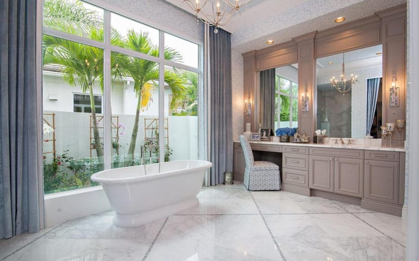 Traditional bathroom with pedestal bathtub with window views