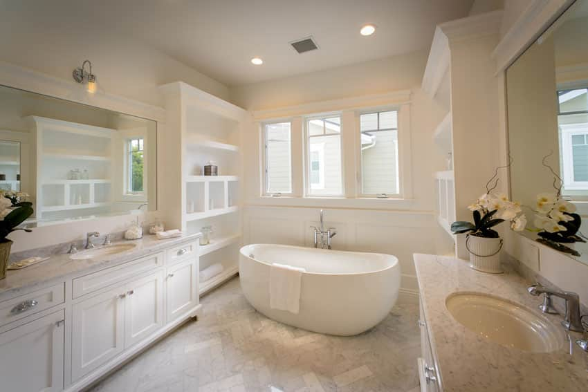 Traditional master bathroom with soaking bathtub and white vanities with marble counters