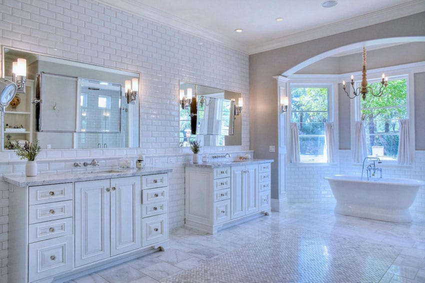 White master bathroom with subway tile and acrylic bathtub with window views