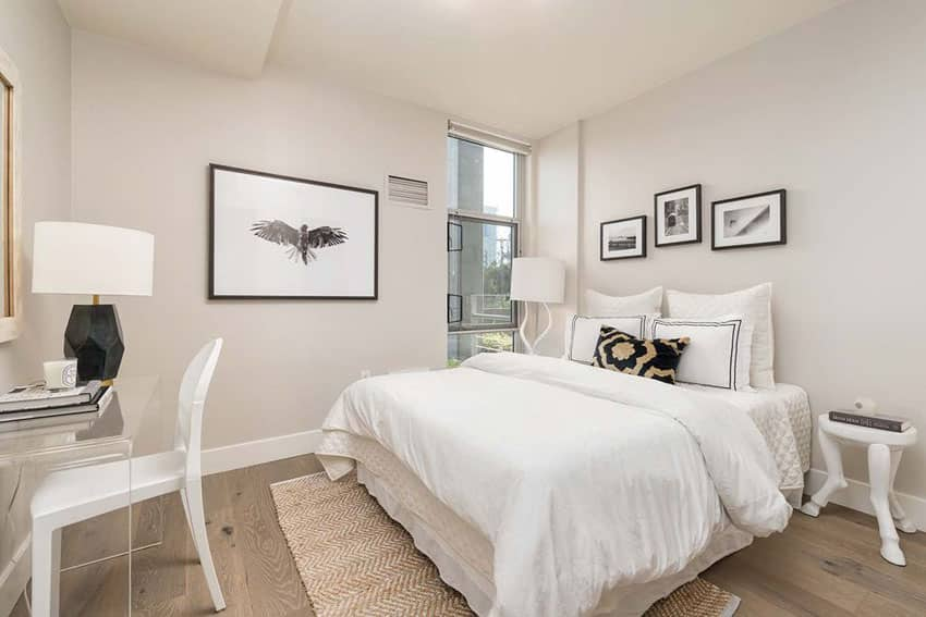 Bright guest bedroom with white furniture and wood floors