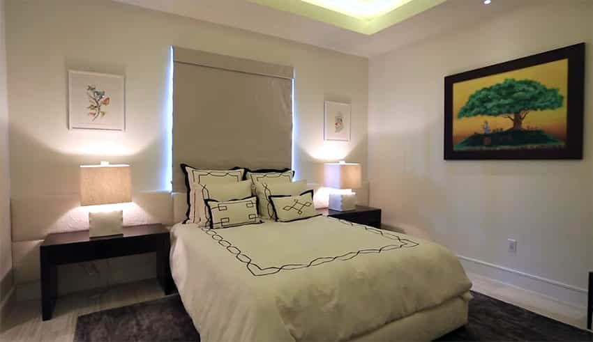 Decorated guest bedroom with light wood floors
