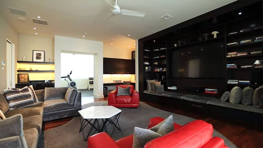 Family room with large black modern entertainment center with bench seating