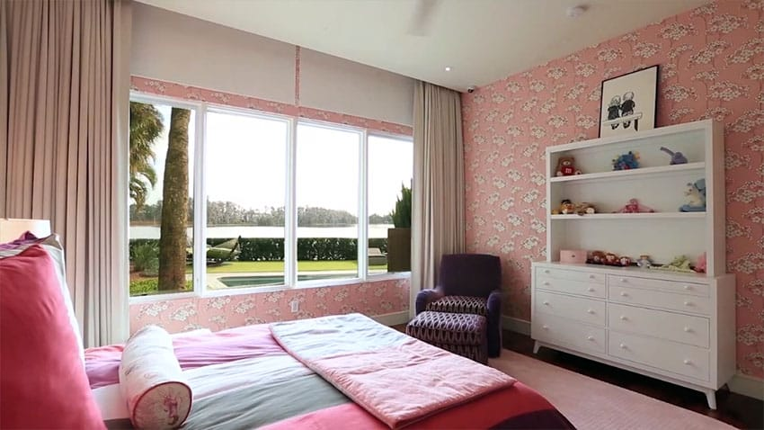 Girls pink and white bedroom with wallpaper and purple chair
