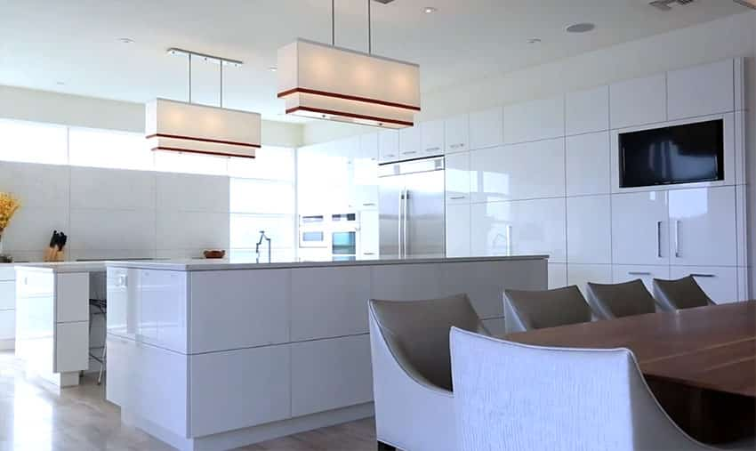 Large open concept white modern kitchen with high gloss cabinets and two islands
