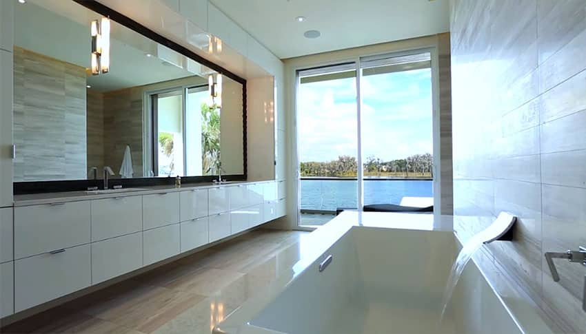 Modern bathroom with white gloss cabinets and lake views