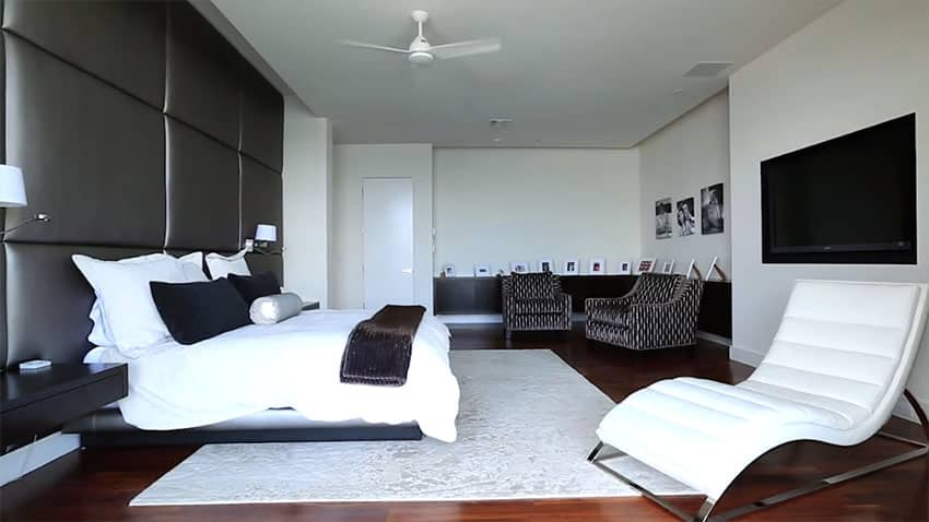 Modern black and white bedroom design with wall sized leather headboard