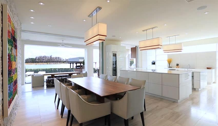 Modern dining room with lake views open to white gloss cabinet kitchen