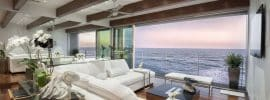 ocean-view-contemporary-living-room-with-sliding-glass-doors-wood-flooring-and-beam-ceiling