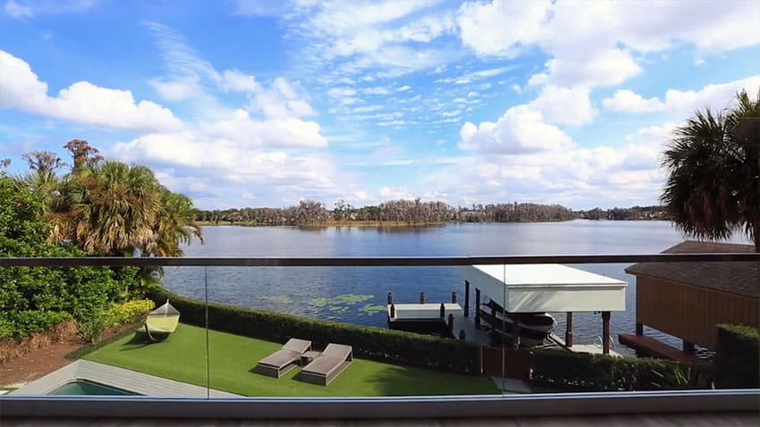 Second story balcony view of lake with glass railing