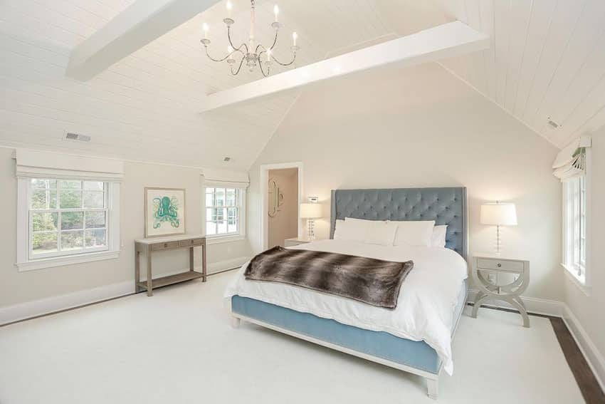 Traditional white bedroom with blue tufted headboard and bed frame