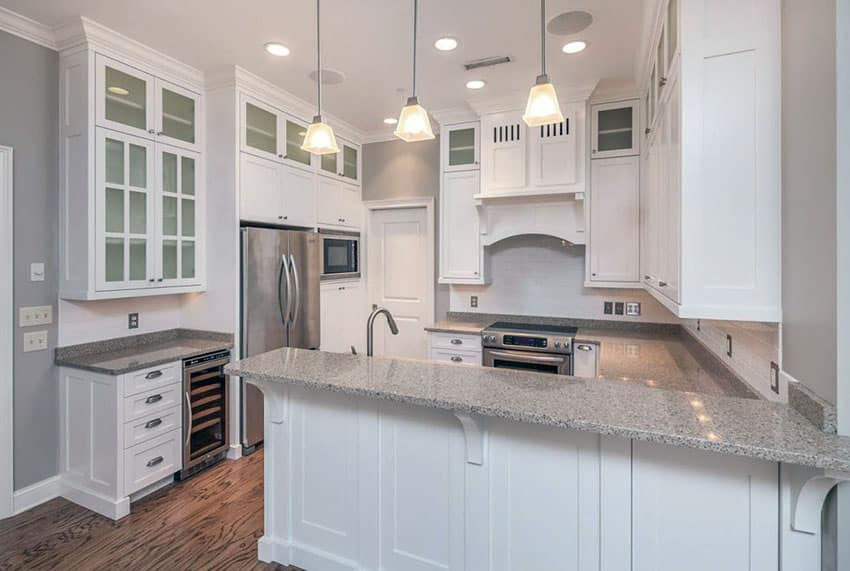 Traditional White Cabinet Kitchen With Peninsula Granite Counters And Pendant Lighting