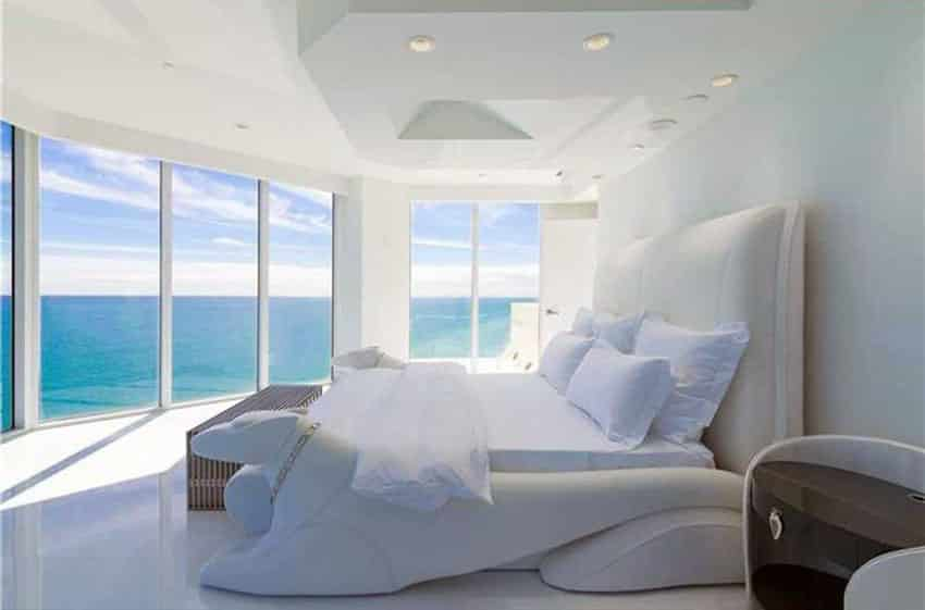 White bedroom with ocean views and custom bed frame