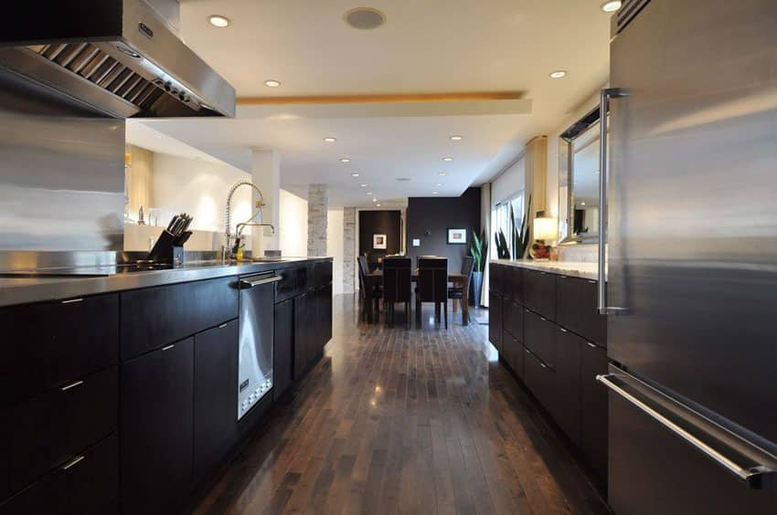 Contemporary dark cabinet galley style kitchen with wood flooring