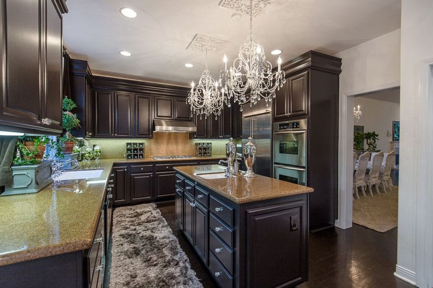 Dark cabinet traditional kitchen with beige granite counters and two chandeliers