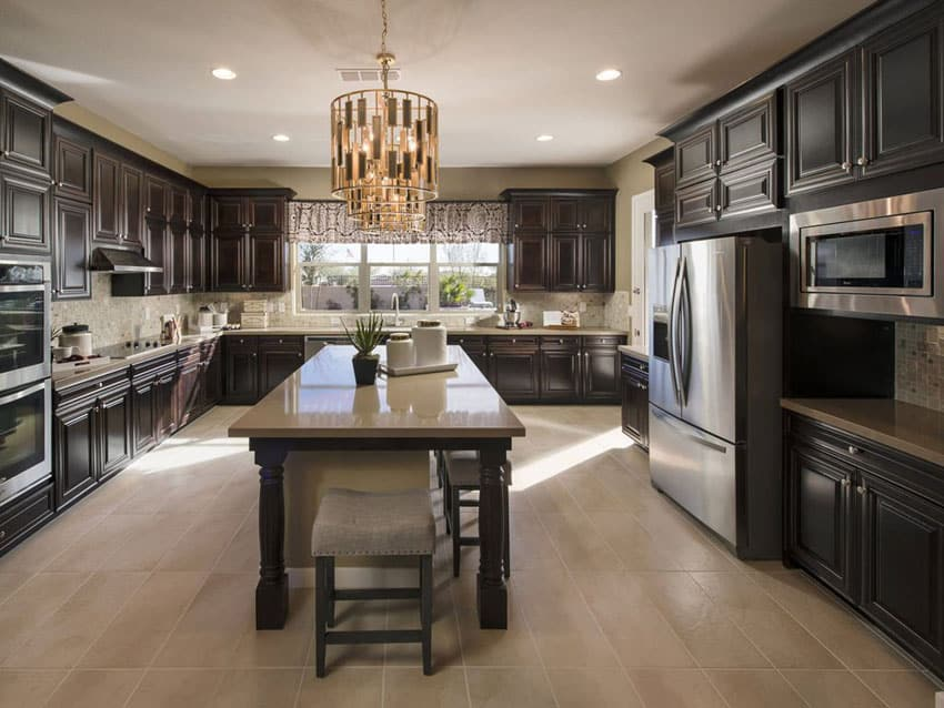Kitchen with dark raised panel cabinets, quartz counter island and porcelain floor tiles