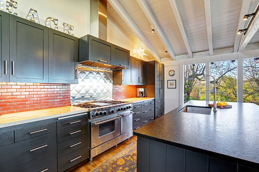 Modern kitchen with black cabinets, small brick backsplash, vaulted wood ceiling, and butcher block counter