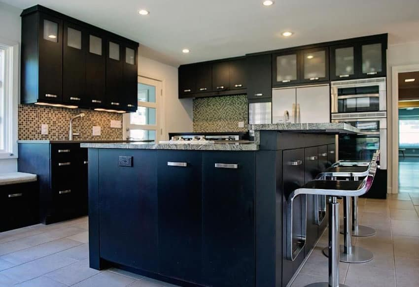 Modern kitchen with black glass cabinets, two tier island, bar stools and glass backsplash