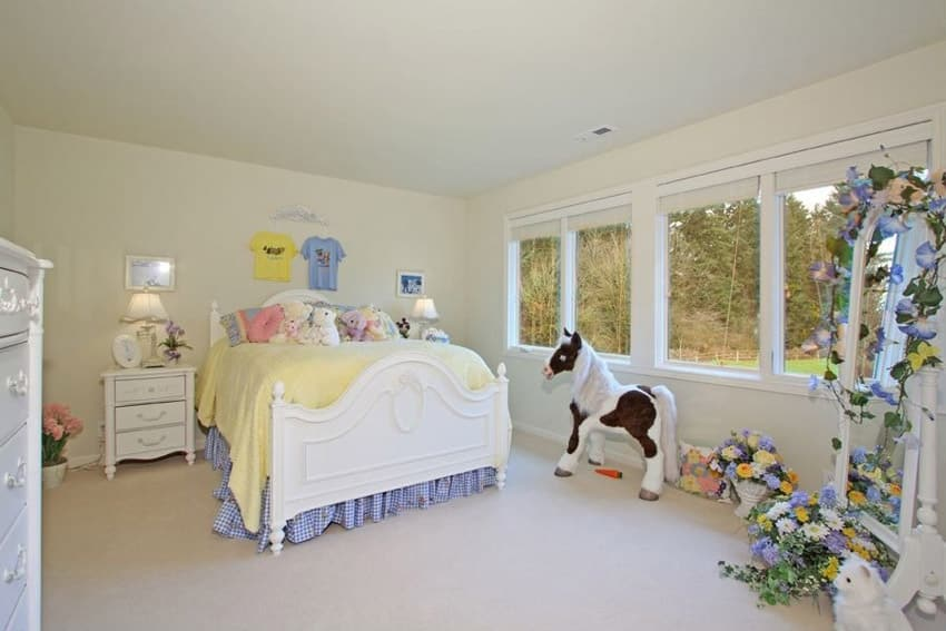 Girls bedroom with white decorative bed frame and backyard view